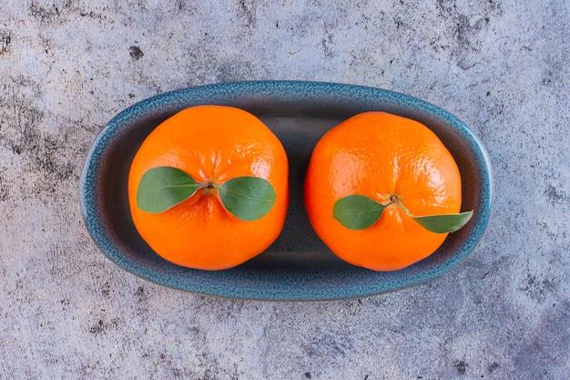 Vista dall'alto di due mandarini freschi con foglie sul piatto di legno su grigio.