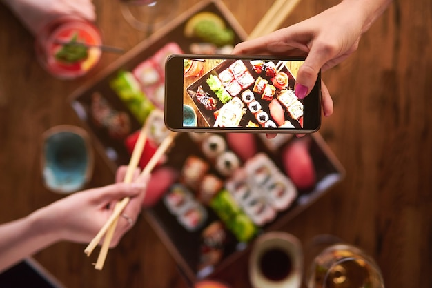 Top of view. two girls are eating sushi and take pictures on smartphone. set of various types of rolls and sushi with drinks