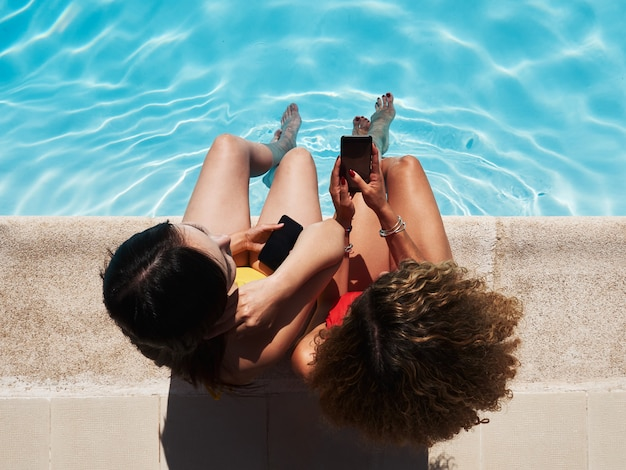 Top view of two girls sitting at the edge of the pool watching the mobile phone