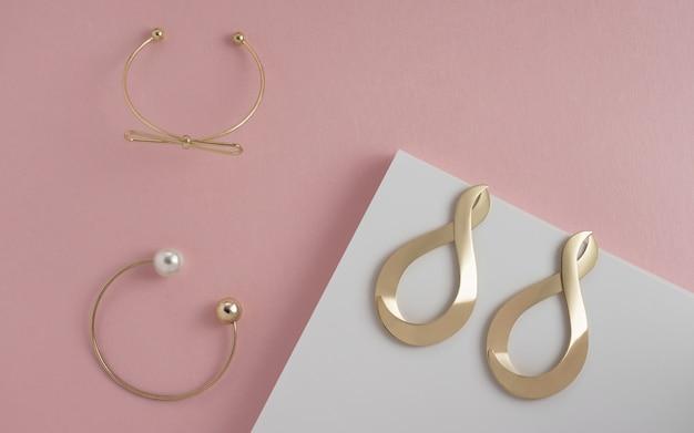 Top view of two golden bracelet and modern earrings pair on pink and white pastel colors wall