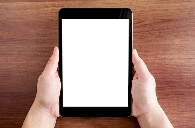 Top view of two hand holding tablet with blank white screen on dark brown wooden table top