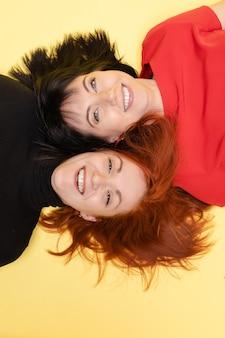 Vista dall'alto di due donne gioviali felici in rosso e nero che sorridono felicemente alla telecamera su giallo. due donne ottimiste con i capelli rossi e scuri che ridono sdraiate sul pavimento.