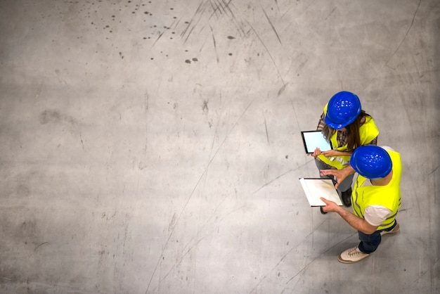 Top view of two industrial workers wearing hardhats and reflective jackets holding tablet and checklist on gray concrete floor