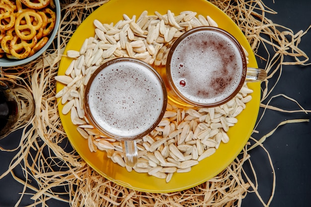 Top view of two mugs of beer on a plate with sunflower seeds on straw