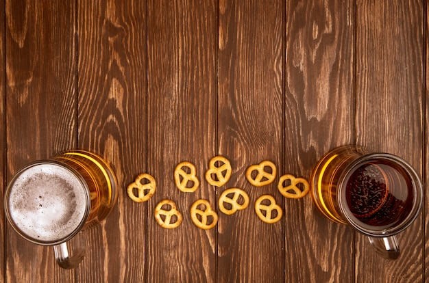 Top view of two mugs of beer with mini pretzels on sackcloth on rustic with copy space