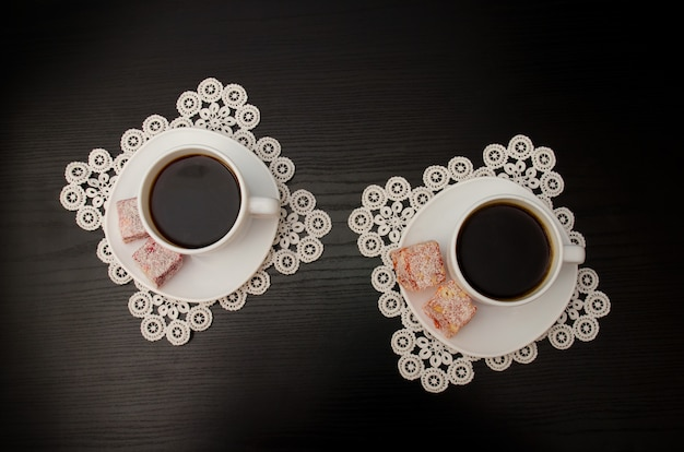 Top view of two mugs of coffee on a saucer with turkish delight. lacy napkins, black table