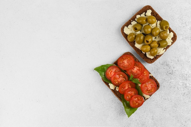 Top view two open faced sandwiches with feta cheese, tomato with basil and olives on light stone background with copy space