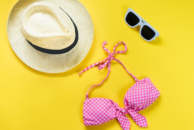 Top view of two pieces pink chequered swimming suit, white sunglasses and straw hat on yellow