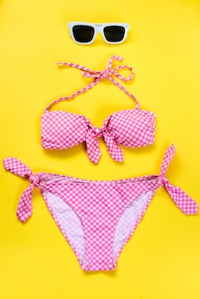 Top view of two pieces pink chequered swimming suit and white sunglasses on yellow