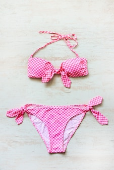 Top view of two pieces pink chequered swimming suit on wooden