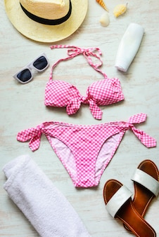 Top view of two pieces pink swimming suit and beach accessoties on wood.