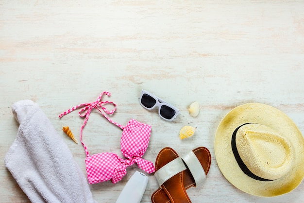 Top view of two pieces pink swimming suit and beach accessoties on wooden background. copy space