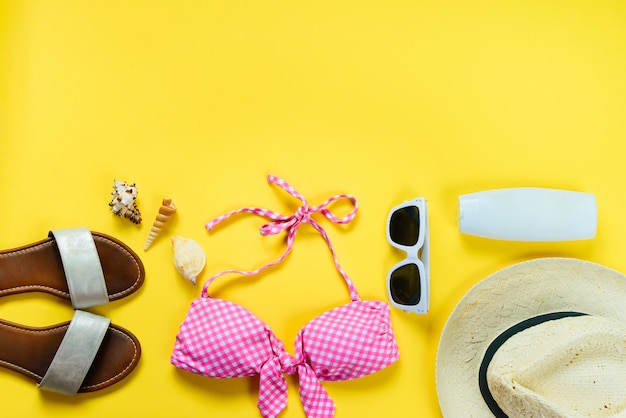 Top view of two pieces pink swimming suit and beach accessoties on yellow background.