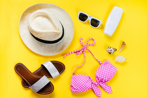 Top view of two pieces pink swimming suit and beach accessoties on yellow