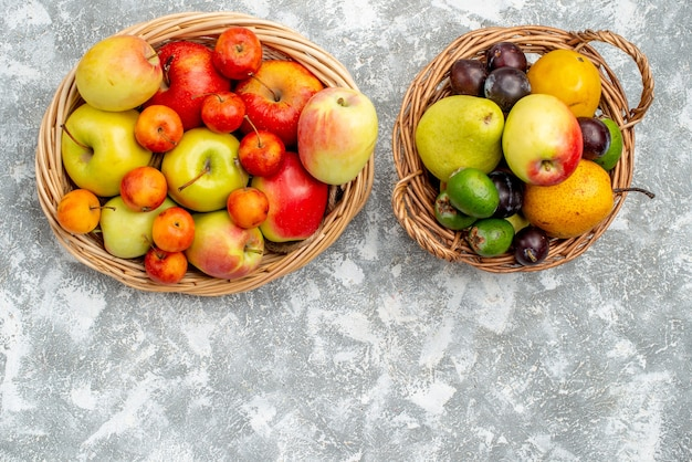Vista dall'alto due cesti di vimini di plastica con mele rosse e gialle e prugne pere feykhoas e cachi sul tavolo grigio