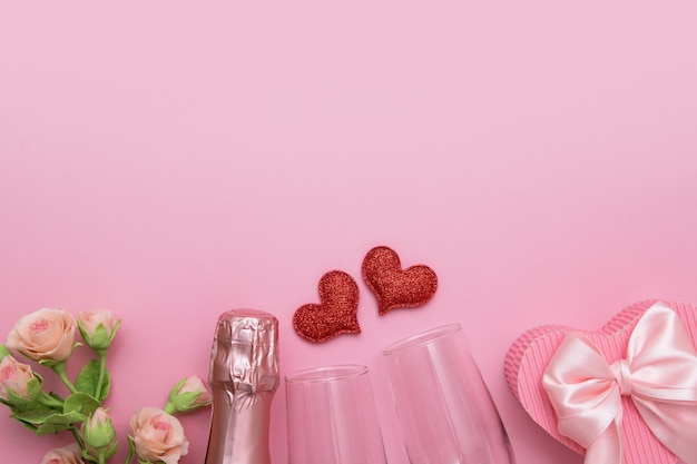 Top view two red hearts, glasses, champagne, flowers on a pink background with copy space valentines day date or party concept