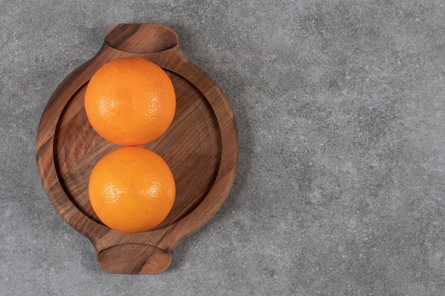 Top view of two ripe oranges on wooden tray over grey table.