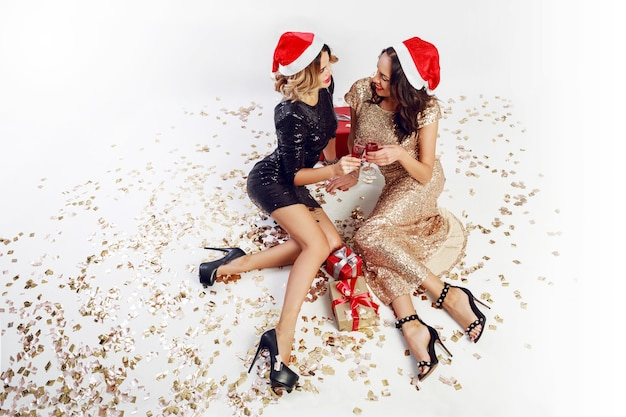 Top view on two   sexy women in  in red christmas santa claus holiday hat sitting on floor with shining golden confetti.  wearing  sparkly  evening  dress.