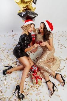 Vista dall'alto su due donne sexy in cappello rosso di festa di babbo natale di natale seduto sul pavimento con brillanti coriandoli dorati. indossare un abito da sera scintillante.