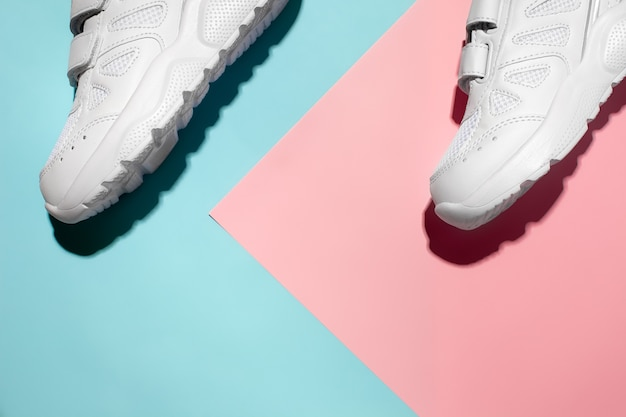 Top view two white sneakers on a delicate geometric paper pink and blue background with hard sunligh...