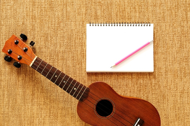 Top view of ukulele with notebook and pencil