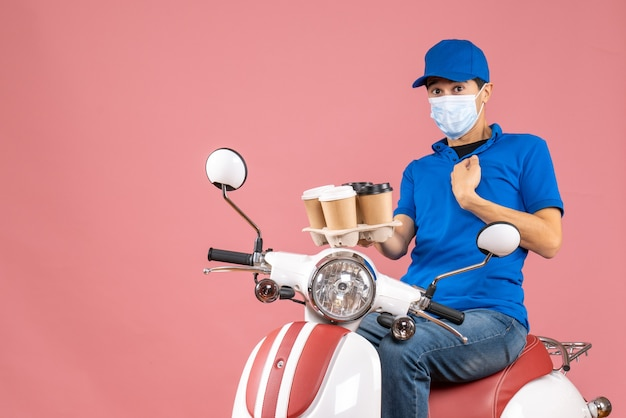 Top view of uncertain unsure courier man in mask wearing hat sitting on scooter showing orders on pastel peach