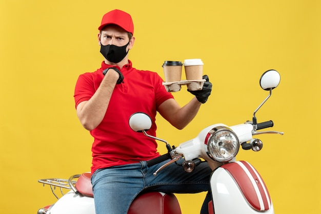 Top view of uncertain unsure delivery man wearing uniform and hat gloves in medical mask sitting on scooter showing orders pointing himself