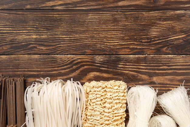 Top view uncooked assortment of noodles on wooden background with copy space