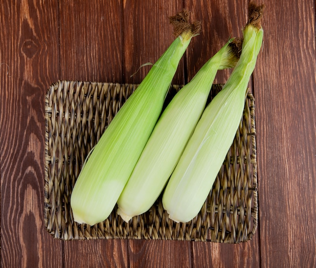 Top view of uncooked corns in basket plate on wooden surface