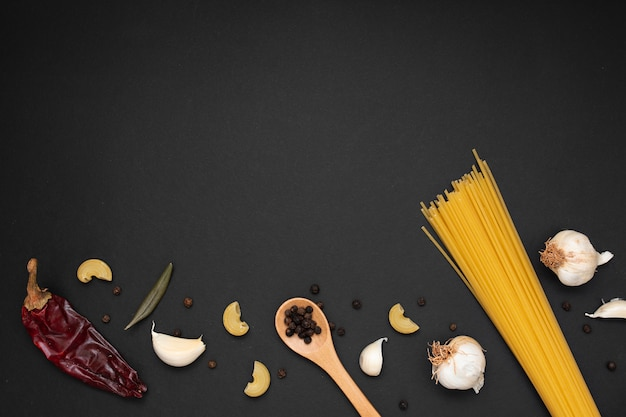 Top view uncooked pasta with wooden spoon ingredients and copy space