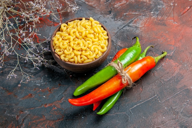 Top view of uncooked pastas cayenne peppers in different colors and sizes tied in one another with rope on mixed color background
