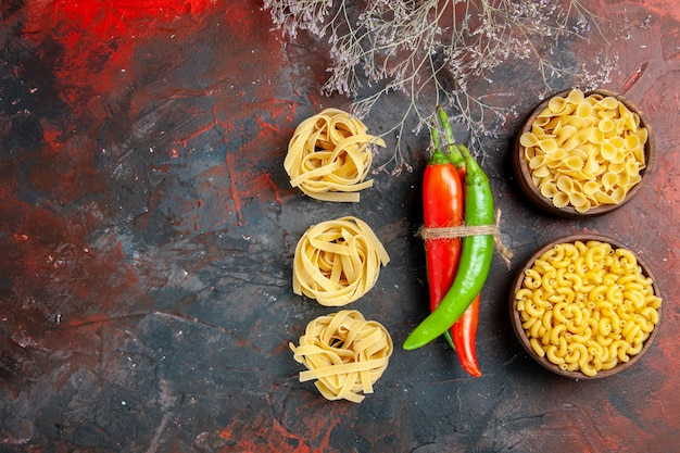 Top view of uncooked pastas cayenne peppers in different colors and sizes tied in one another with rope on mixed color table