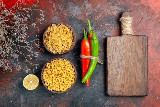 Top view of uncooked pastas cayenne peppers in different colors and sizes tied in one another with rope and wooden cutting board on mixed color background