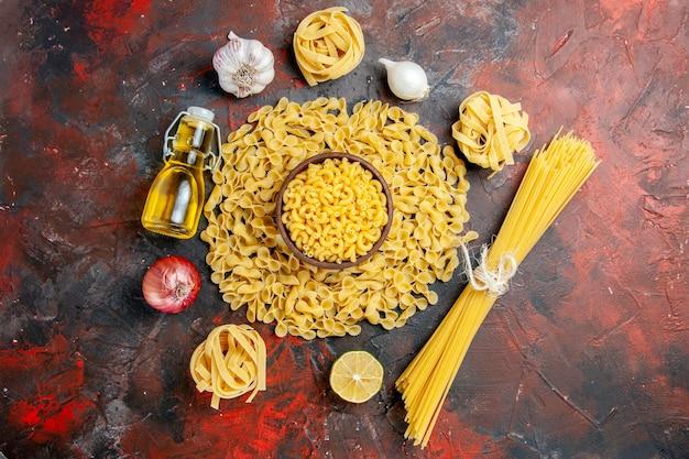 Vista dall'alto di pasta cruda in varie forme come spaggeti aglio e cipolla bottiglia di olio su sfondo di colore misto