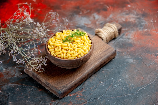Top view of uncooked pastas on wooden cutting board on mixed color background