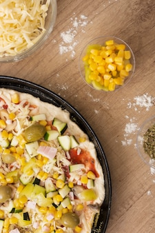 Top view uncooked pizza in pan with corn