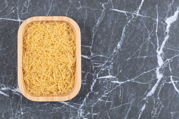 Top view of uncooked raw vermicelli on wooden plate.