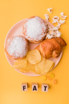 Top view unhealthy snacks with fat letters