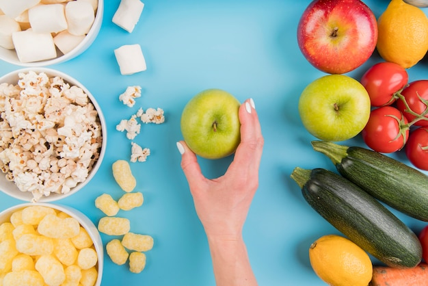 Top view unhealthy vs healthy food with hand holding apple