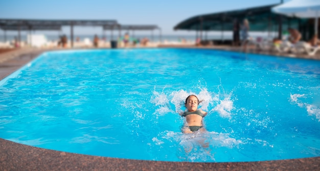 Вид сверху неопознанной хорошенькой молодой девушки, счастливо плещущейся в голубой чистой воде в бассейне под лучами яркого солнечного света. концепция отдыха в отеле и на море. место для рекламы