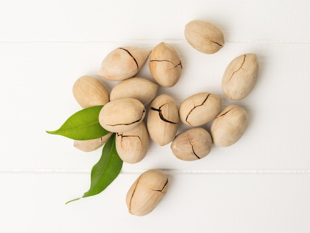 Top view of unpeeled pecans scattered on a white wooden table. vegetarian food.