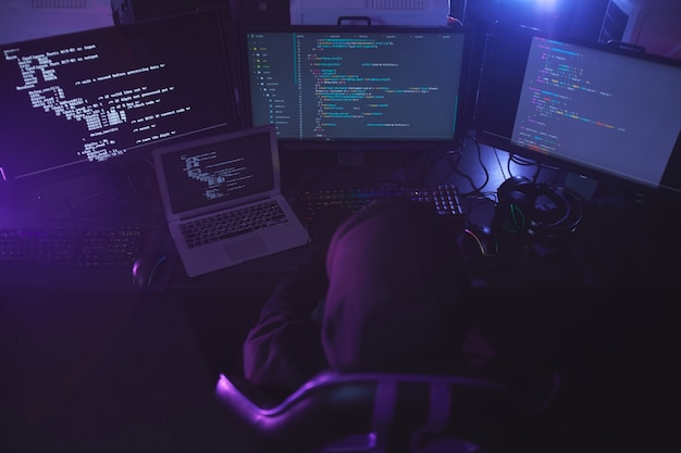 Top view at unrecognizable cyber security hacker wearing hood while working on programming code in dark room, copy space