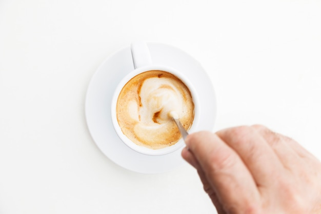 Top view of unrecognizable man dissolving sugar with spoon on cup of coffee.