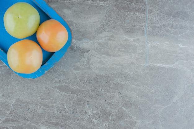 Vista dall'alto di pomodori acerbi in piatto di legno blu su sfondo grigio.