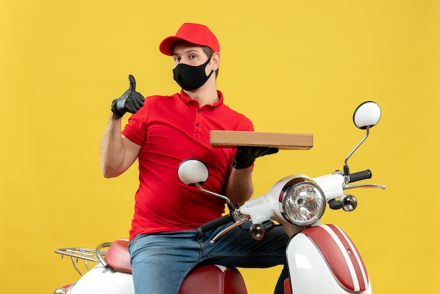 Top view of unsatisfied courier man wearing red blouse and hat gloves in medical mask sitting on scooter showing order making ok gesture