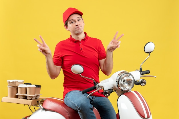Top view of unsatisfied young guy wearing red blouse and hat delivering orders making victory gesture on yellow wall