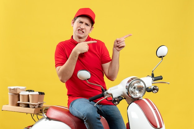 Top view of unsatisfied young guy wearing red blouse and hat delivering orders pointing something on yellow wall