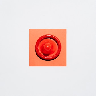 白い背景の上のトップビューラップされていない赤いコンドーム