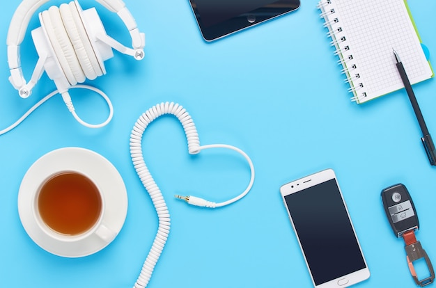 Top view upon gadgets on blue background, composition of white headphones, phone, tablet, glass with a drink and car keys
