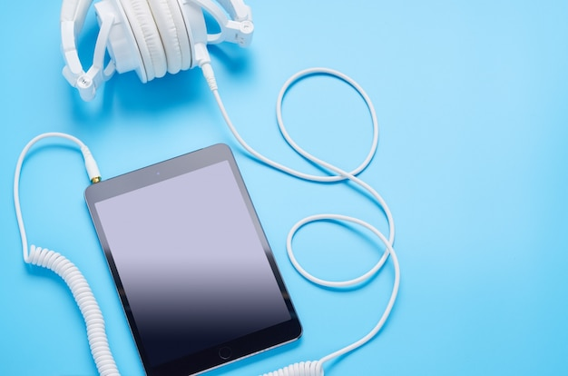 Top view upon gadgets on blue background, composition of white headphones and tablet